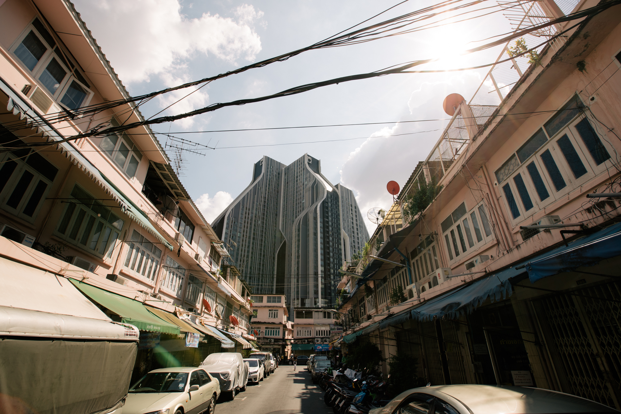Photo of a street in Thailand with buildings on both sides by Imagine Thailand
