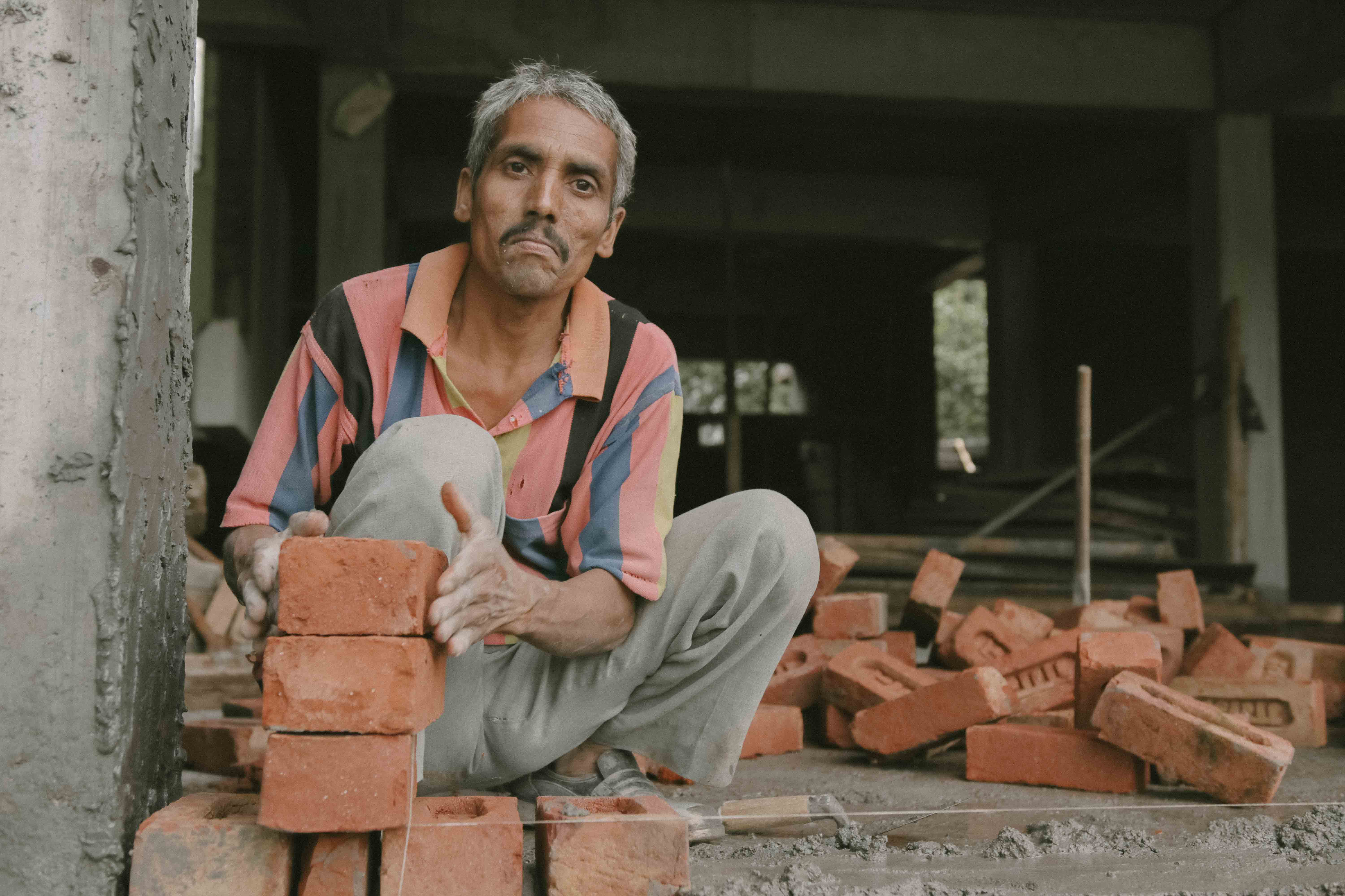 Photo of a man with a stack of bricks in front of him from India.