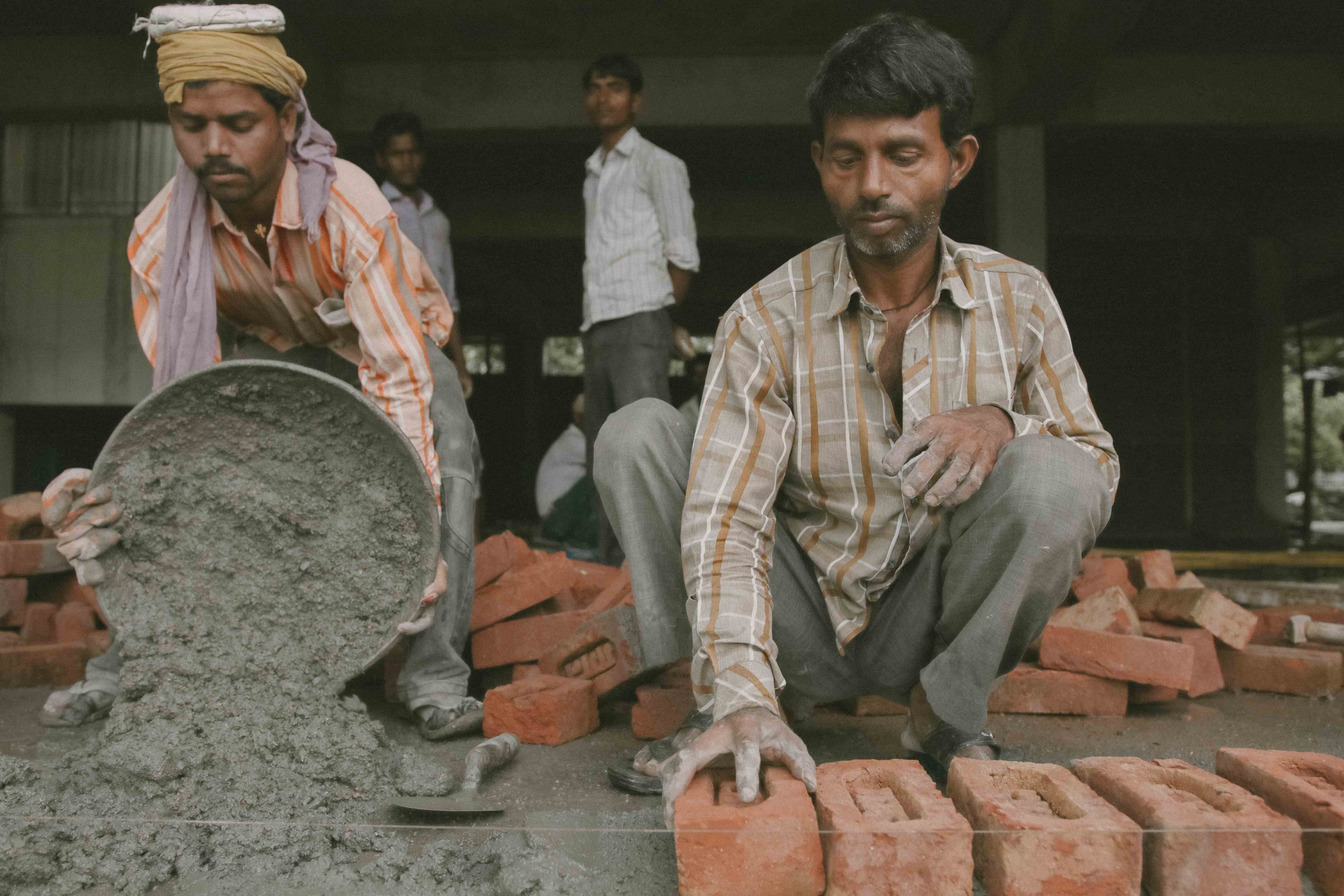 Photo of two men working on brick work from India.