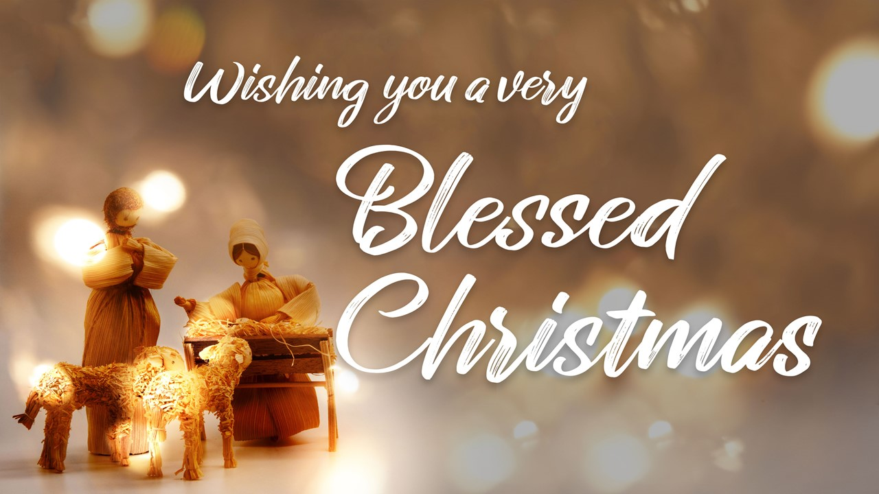 "Stock image of a Nativity scene made with corn husk dolls, with the words ""Wishing You A Very Blessed Christmas"" displayed"
